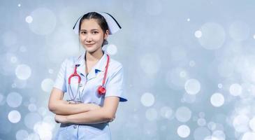 la enfermera estaba de pie con los brazos cruzados sobre un fondo blanco. foto