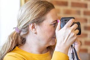 primer plano, mujer, con, un, cámara, en, ella, manos, tomar fotografías foto