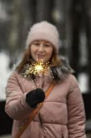 Christmas lights are bright splashes burning in the hands of a blurry happy woman in the park. Sparkler. Emotions, New Year's mood.Winter holidays photo