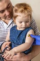 Vaccination of a little girl in her dad's arms in the doctor's office from the coronavirus. Children's funny adhesive plaster. Vaccine against covid-19, flu, infectious diseases. photo