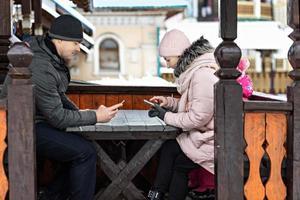 una pareja está esperando su pedido para el almuerzo en un café de la calle, enviando mensajes de texto por teléfono. comunicación con personas en un teléfono inteligente. foto