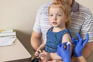 A little girl with her father in the doctor's office at the clinic is being vaccinated against the coronavirus.The concept of vaccination, immunization, prevention against Covid-19. photo