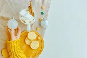 chica sostiene bola de Navidad, taza de cacao, galletas y mantel sobre la mesa. foto