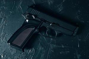 pistola en la mesa de textura de hormigón verde. foto