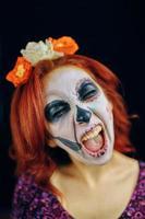 mujer joven en el día de la máscara muerta arte de la cara del cráneo. foto