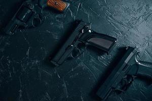 Three guns on black table. photo