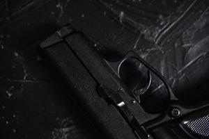 pistola en la mesa de textura negra. foto