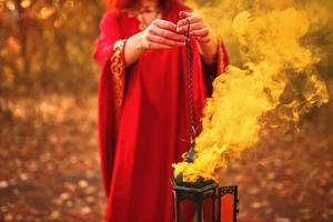 Woman in a red robe holds a lamp from which red smoke is coming photo