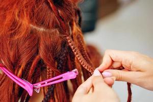 Hairdresser's hands braid girl's ginger dreadlocks. photo