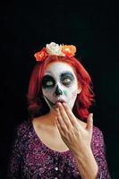 una mujer joven en el día de los muertos máscara cráneo cara arte. foto