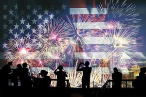 Silhouettes of people looking at fireworks and United States of America flag photo