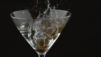 Toma de cámara lenta de aceitunas salpicando en martini toma en phantom flex 4k a 1000 fps video