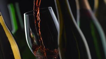 Toma de cámara lenta de vino tinto con botellas y fondo negro en phantom flex 4k a 1000 fps video