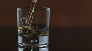 El whisky se vierte en un vaso en cámara lenta filmada en phantom flex 4k a 1000 fps video
