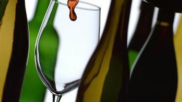 Verter el vino tinto en cámara lenta con botellas en el fondo filmado en phantom flex 4k a 1000 fps video