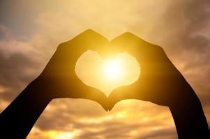 The hands of women and men are the heart shape with the sun light passing through the hands photo