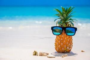 Glasses pineapples are located on the beach by the sea in the hot sun, setting the concept for summer. photo