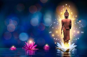 The Buddha statue stands on a white and pink lotus in the water. Bokeh blue background. photo