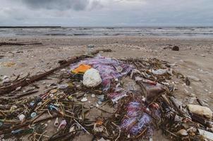 basura la playa mar botella de plástico se encuentra en la playa y contamina el mar y la vida marina basura derramada en la playa de la gran ciudad. Botellas de plástico sucias usadas vacías foto