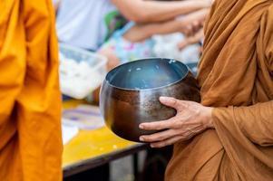 las limosnas en torno a las túnicas amarillas de los monjes caminan sobre las limosnas como una actividad budista. foto