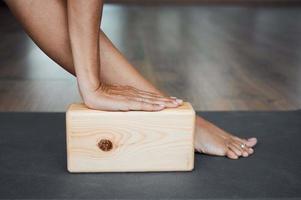 Pose de triángulo extendido con primer plano de ladrillo, pose de utthita trikonasana con bloque de madera en yoga iyengar en estudio foto