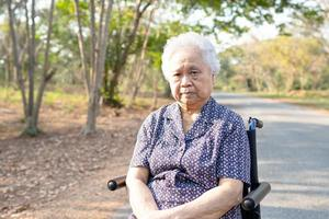 Asian senior or elderly old lady woman patient on wheelchair in park photo