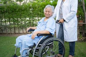 Doctor help and care Asian senior or elderly old lady woman patient sitting on wheelchair at park in nursing hospital ward, healthy strong medical concept. photo