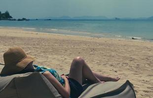 young woman lying on bean bag at beach to take sunbath on summer vacation photo