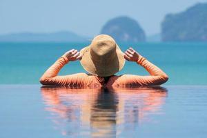 retrato, de, mujer joven, llevando, sombrero de paja, y, traje de baño, posición, en, el, azul, piscina infinita, mirar la vista, de, ocian, en, vacaciones de verano foto