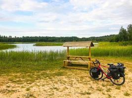 Bicicleta de turismo completamente cargada de pie junto a la mesa de madera con fondo del lago. Bicicleta de turismo en la campiña de Lituania. foto