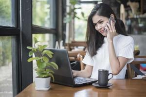 Beautiful business girl working with tablet , smartphone and drinking coffee in coffee shop photo