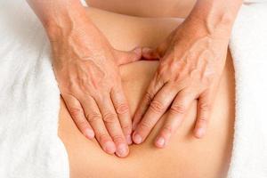Massage Therapist Massaging a Womans Stomach photo