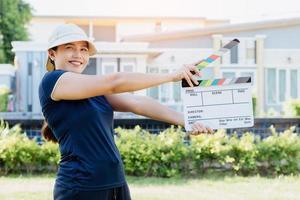 Mujer asiática sosteniendo el tablero de colores de pizarra de película para la industria del cine y la televisión foto