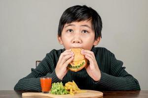 lindo niño asiático comiendo una deliciosa hamburguesa con felicidad foto