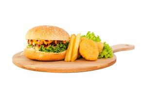 Chicken hamburger with nuggets and french fries on a wooden plate over white background photo