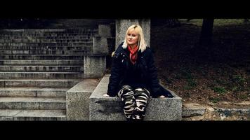 A blonde woman with red scarf sitting on the stone stairs and looking at the camera. photo