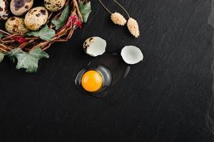 huevos de codorniz sobre fondo de piedra negra, huevo de codorniz roto, agrietado, yema de huevo de codorniz. Producto organico. foto