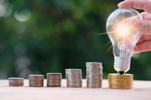 hombre de negocios, mano, tenencia, bombilla de luz, con, dinero, monedas foto
