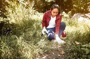 mujer voluntaria sentada y recogiendo basura en el parque. medio ambiente contaminación plástica. el concepto del día mundial del medio ambiente. cero desperdicio. foto