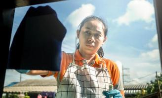 Woman wearing protective gloves cleaning window by spraying cleaning products and wiping with blue rag. Cleaning House concept. photo