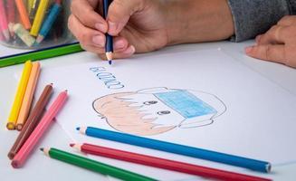 Primer plano de una mano pintada con lápiz de color, representación de un hombre con una máscara contra el coronavirus. foto