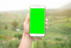 cerca de la mano que sostiene el teléfono inteligente con pantalla en blanco en el fondo de la montaña. foto