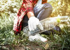 Cerca de voluntarios se sientan y recogen basura en el parque. medio ambiente contaminación plástica. el concepto del día mundial del medio ambiente. cero desperdicio. foto