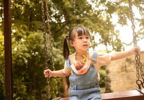 Happy child girl playing swing outdoor in the park on summer time. Concept of Childhood happiness. photo
