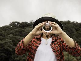 Asian woman  holding and look into a magic crystal glass ball on nature background. photo