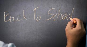 Close-up of a Hand holding a chalk and writing writing Back to school on the Blackboard. Concept of happy to return to school after the quarantine. photo