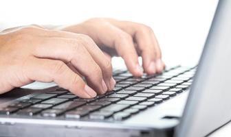 primer plano de la mano ocupada escribiendo en la computadora portátil para trabajar. foto