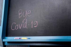 Bye Covid-19 text on a blackboard, written by chalk. photo