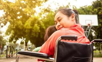 madre feliz en silla de ruedas abrazando a niña sentada en su regazo en el parque. discapacitados, concepto de maternidad. foto