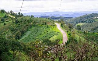camino de tierra para autos hasta el doi mae tho con hermosos árboles y prados verdes, distrito caliente, chiang mai, tailandia. foto